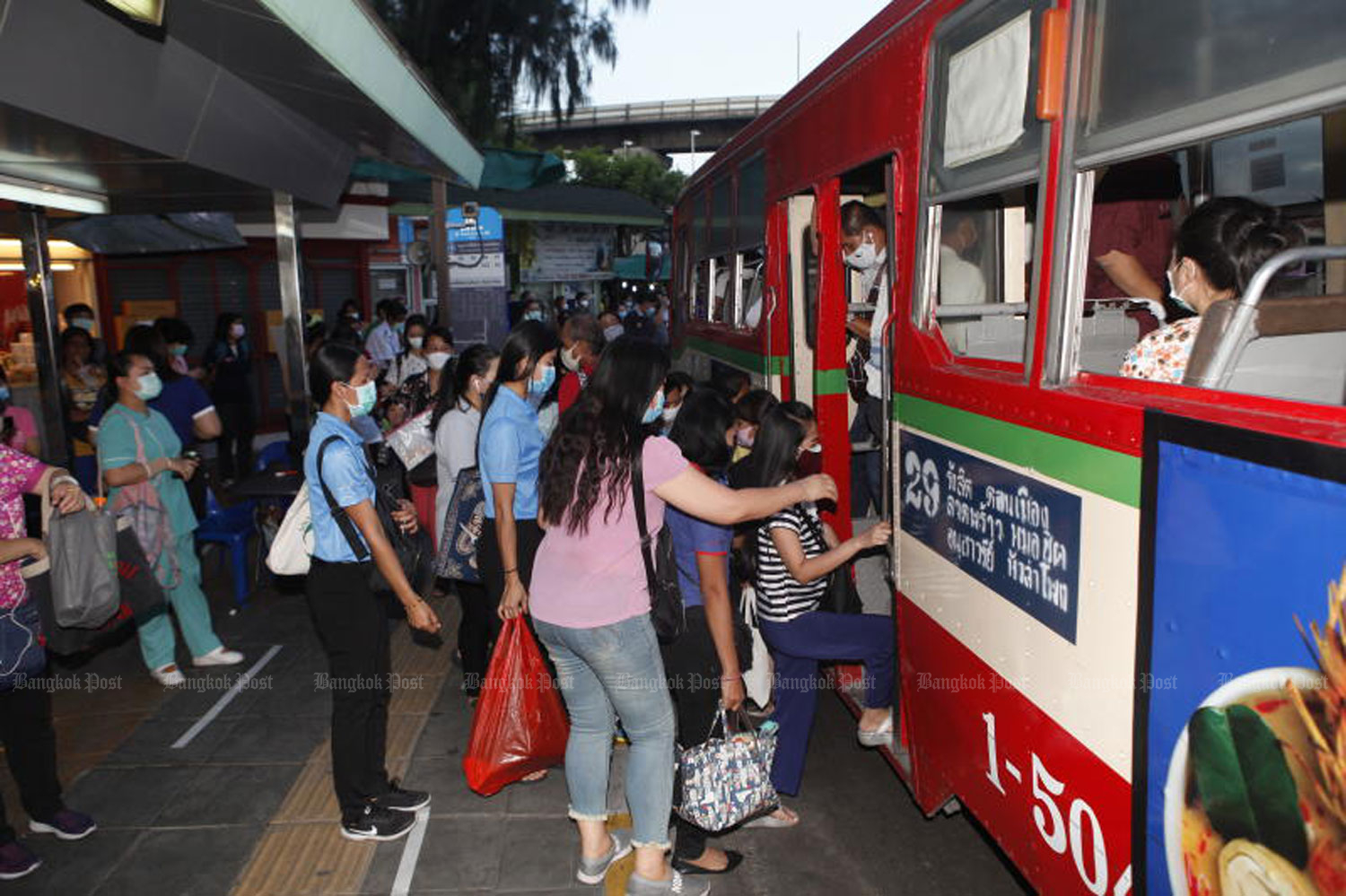 People, wearing face masks, rush to get on a bus to work during morning rush hours at the Victory Monument on May 12. (Photo by Nutthawat Wicheanbut)