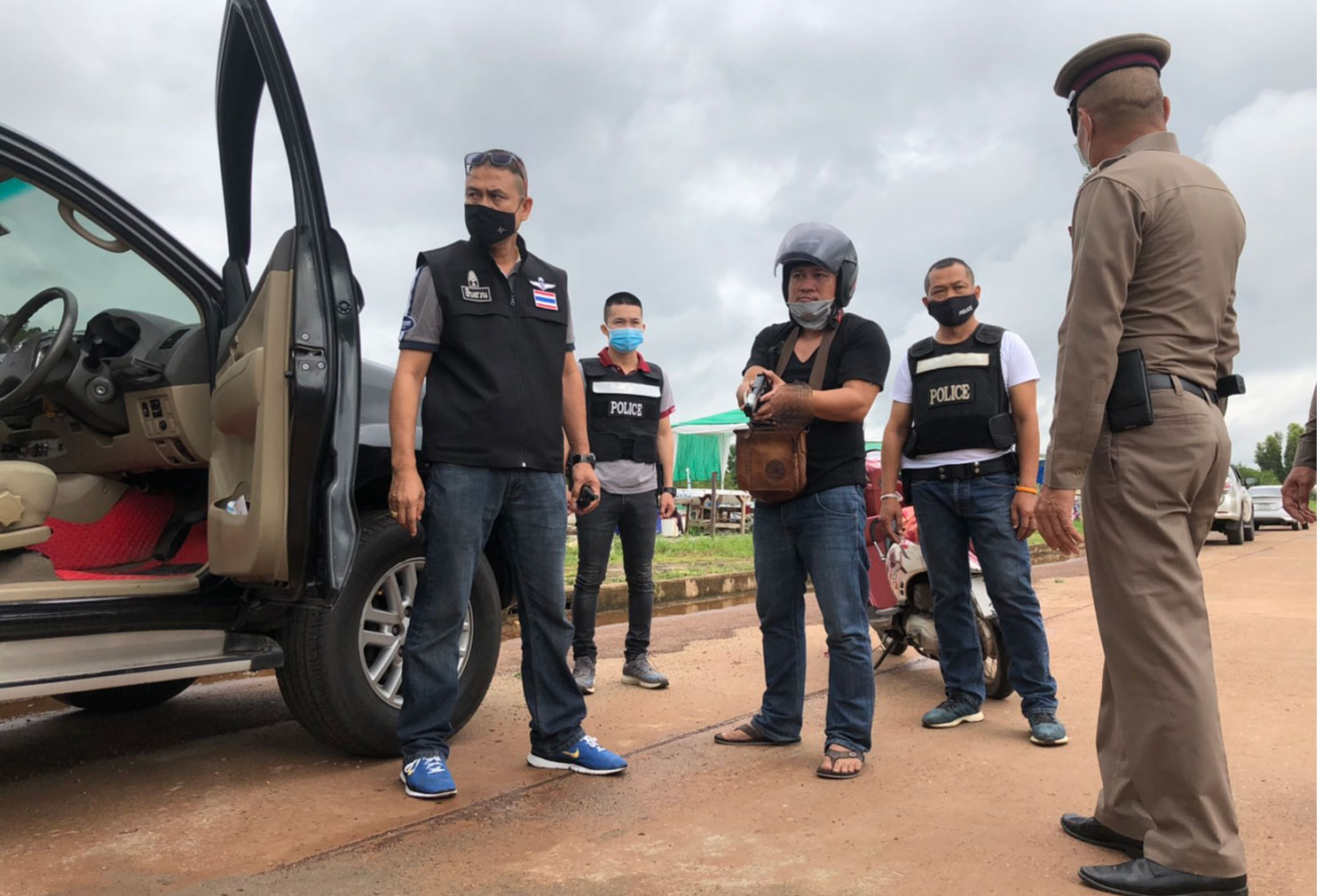 Murder suspect Noppadol Nuamsamlee, wearing a crash helmet, is taken for a crime re-enactment on a road in Muang district of Nakhon Phanom on Saturday. He faces charges of shooting his wife, her sister and their mother to death. (Photo: Pattanapong Sripiachai)