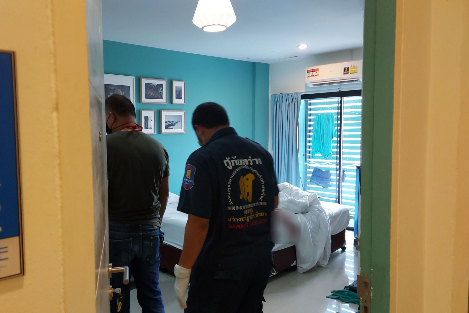 Rescue workers prepare to remove the body of an Australian man from his apartment in Pattaya on Saturday. (Photo: Chaiyot Pupattanapong)