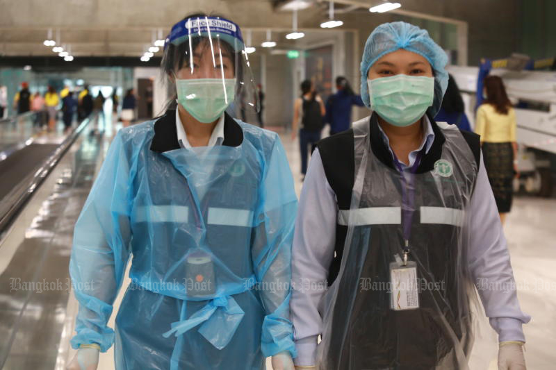Quarantine officials protect themselves from Covid-19 as they walk at Suvarnabhumi airport on Friday. (Photo by Somchai Poomlard)