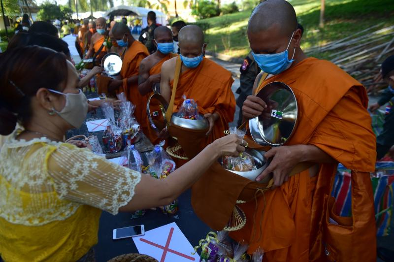 Monks receive food offerings from devotees to mark Asalha Bucha Day in the southern province of Narathiwat on Sunday, amid restrictions due to the Covid-19 coronavirus. (AFP photo)
