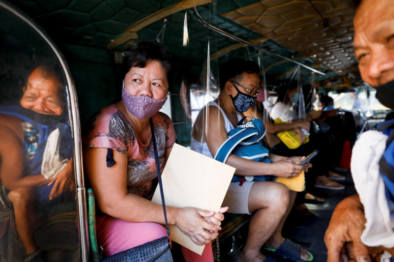 Passengers wearing masks for protection against the coronavirus disease (Covid-19) are seated in between plastic barriers to maintain social distancing in a jeepney, in Quezon City, Metro Manila, Philippines, on Friday. (Reuters photo)