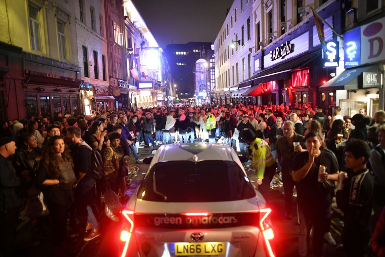 A car tries to drive along a street filled with people drinking in the Soho area of London.