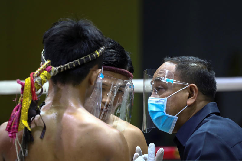 A referee and Muay Thai boxers wearing face shields gather before their fight in front of empty spectator seats behind closed doors due to the spread of the coronavirus disease (Covid-19) at the Siam Boxing Stadium in Samut Sakhon province, on Saturday. (Reuters photo)