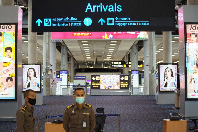 Immigration officers stand in front of an empty arrivals hall at Suvarnabhumi airport amid the spread of the coronavirus disease on Friday. (Reuters photo)