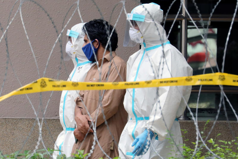 Police officers wearing protective suits pick up an illegal immigrant from an apartment under enhanced lockdown, during the movement control order due to the outbreak of the coronavirus disease (Covid-19), in Kuala Lumpur, Malaysia, May 1, 2020. (Reuters file photo)