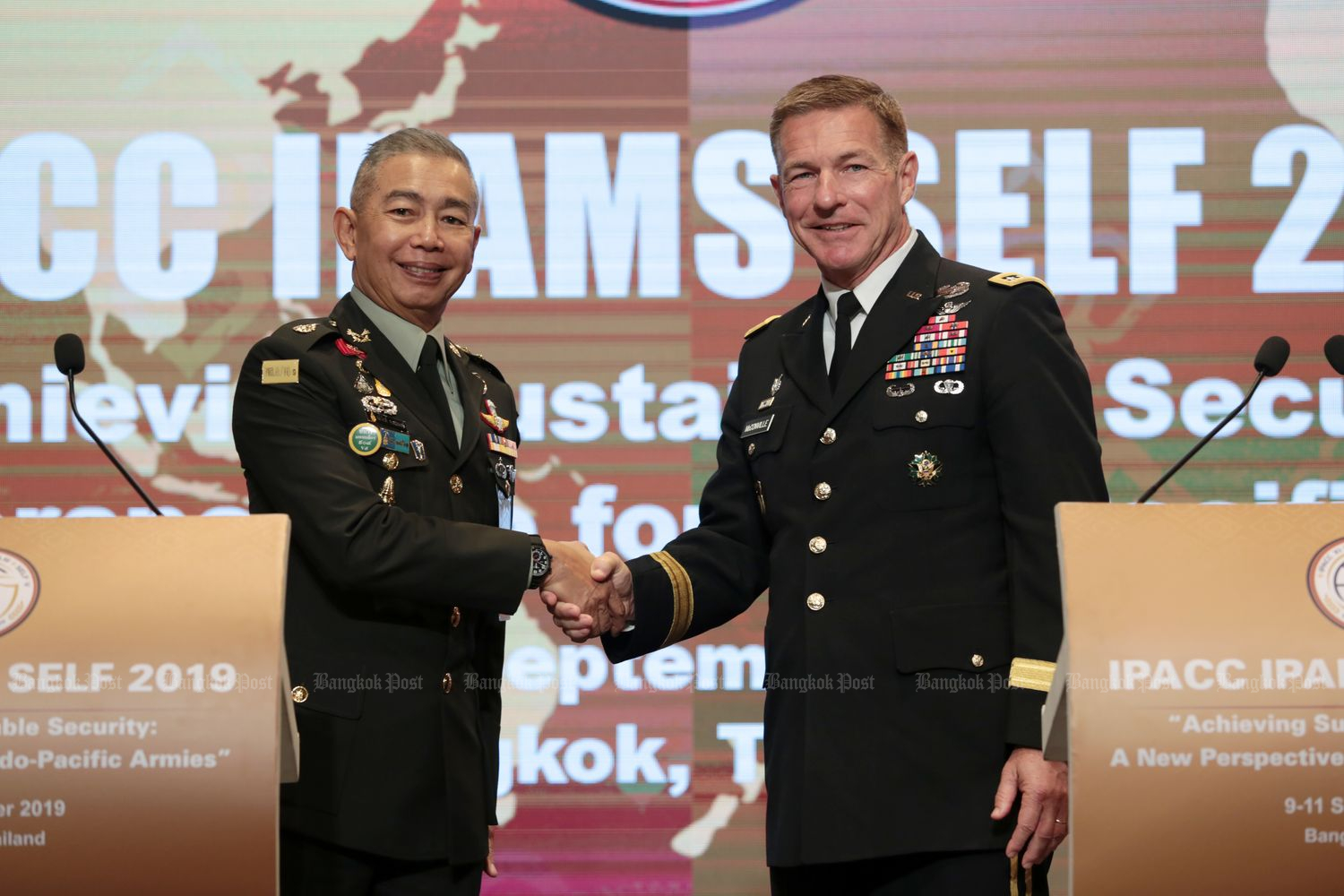Thai army chief Gen Apirat Kongsompong (left) and US army chief of staff Gen James McConville shake hands during the 11th Indo-Pacific Armies Chiefs Conference held in Bangkok in September last year. (Photo by Chanat Katanyu)