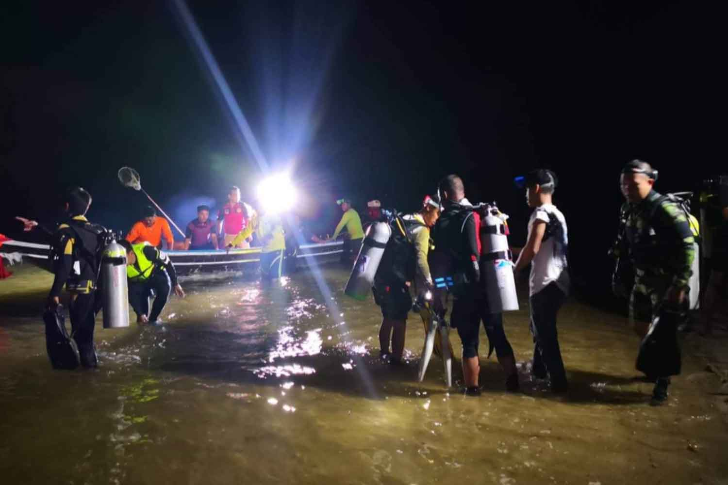 Divers embark on boats at Laem Pho beach in Chaiya district, Surat Thani, on Tuesday night, to search for the young woman swept out to sea while collecting shellfish. (Photo: Supapong Chaolan)
