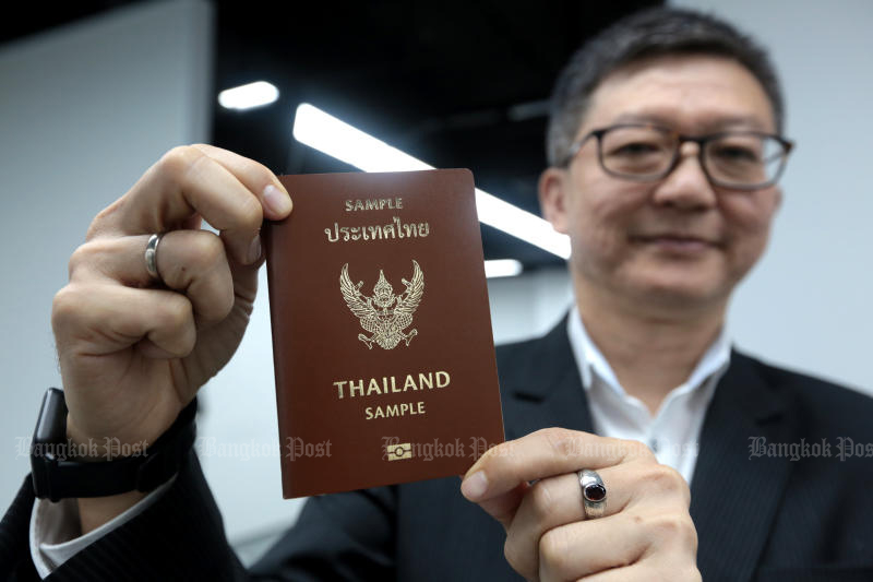 Consular department director-general Chatri Archjananun shows a copy of the new version of the passport on Wednesday, at a passport office in the MBK shopping centre. (Photo:  Chanat Katanyu)