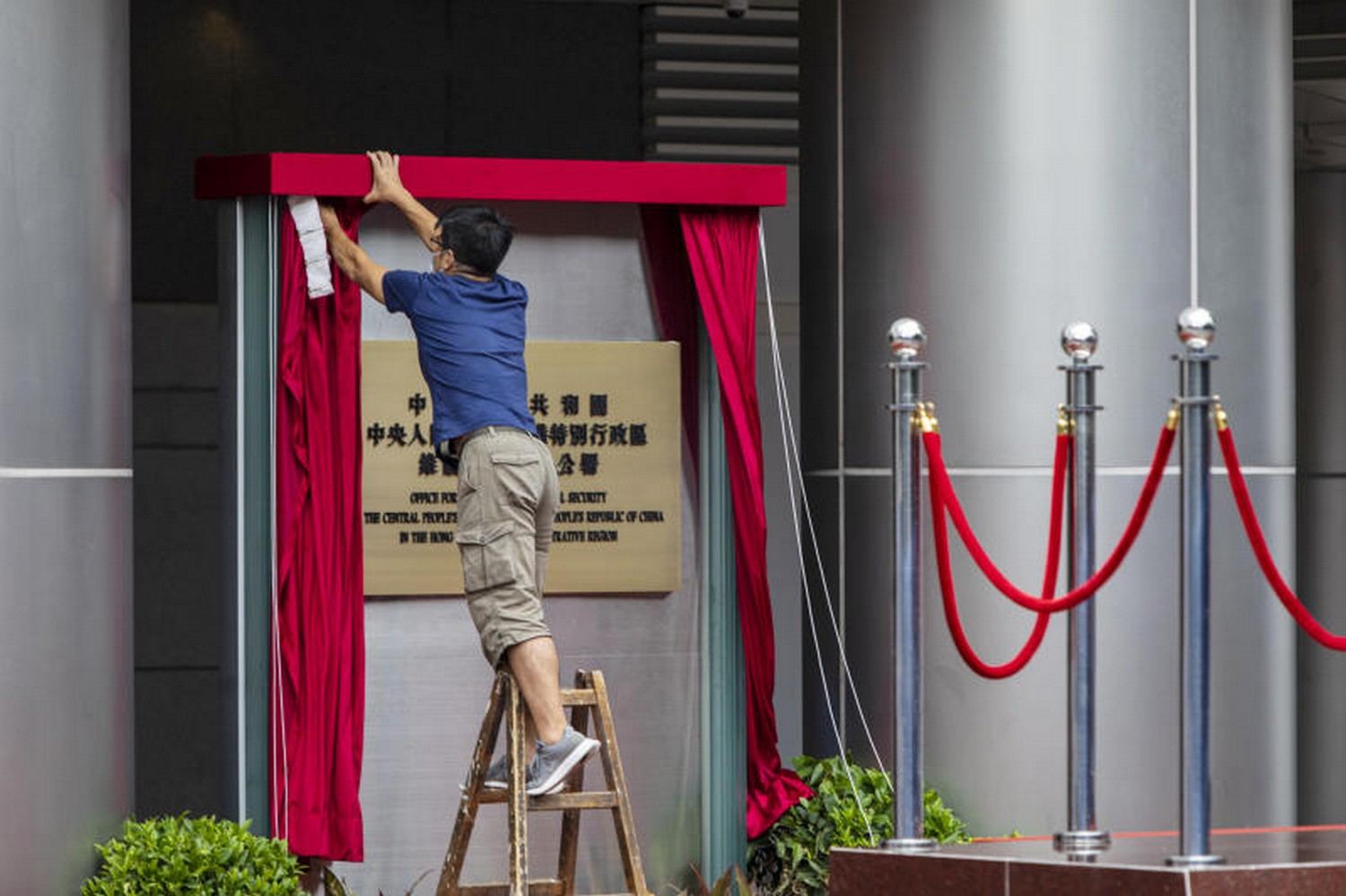 A worker removes a red curtain from the plaque outside the new Office for Safeguarding National Security in Hong Kong, temporarily set up at the Metropark Hotel, on Wednesday. (Photo: Bloomberg)