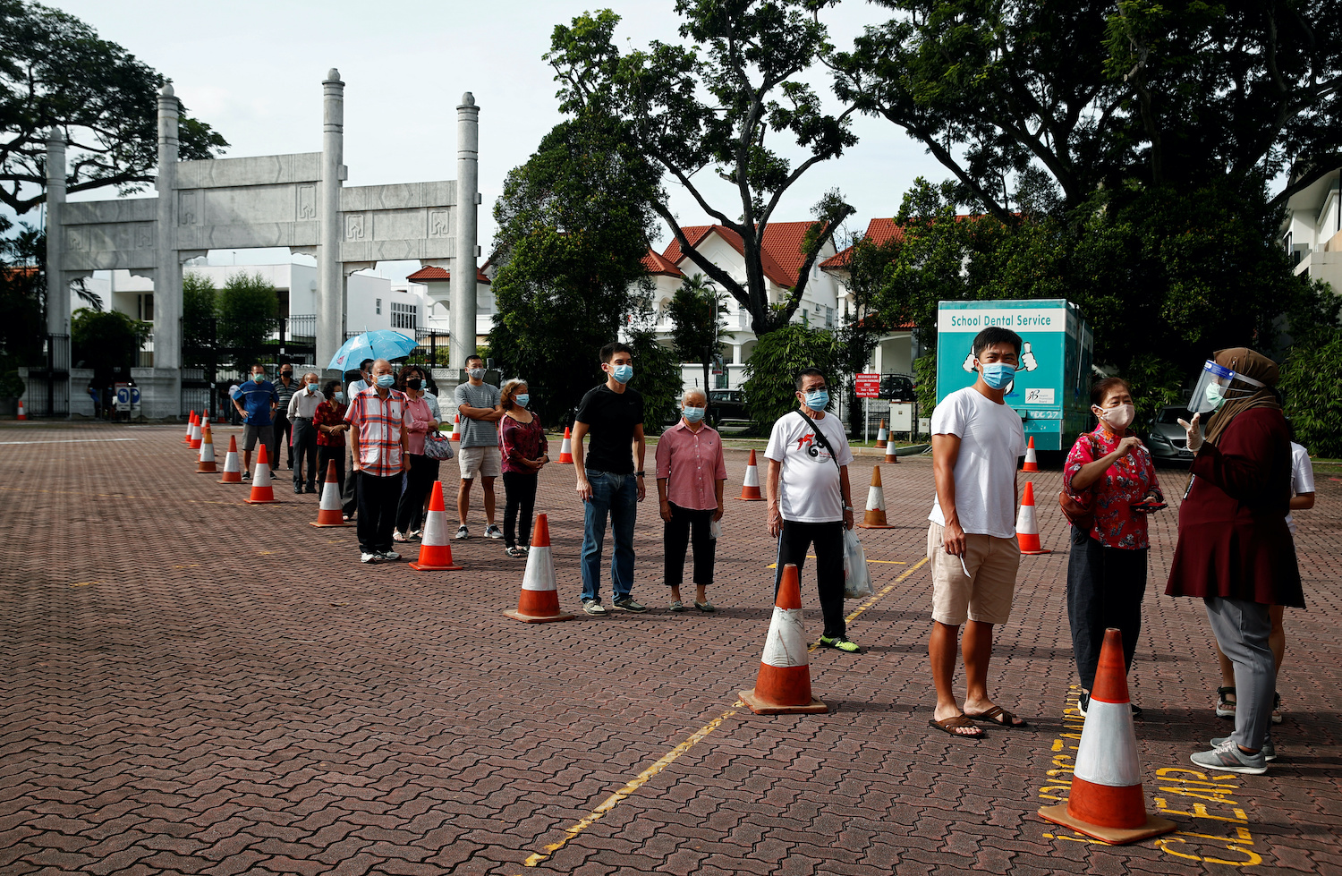 Voters queue at a polling station to cast ballots in Singapore's general election on Friday. (Reuters Photo)
