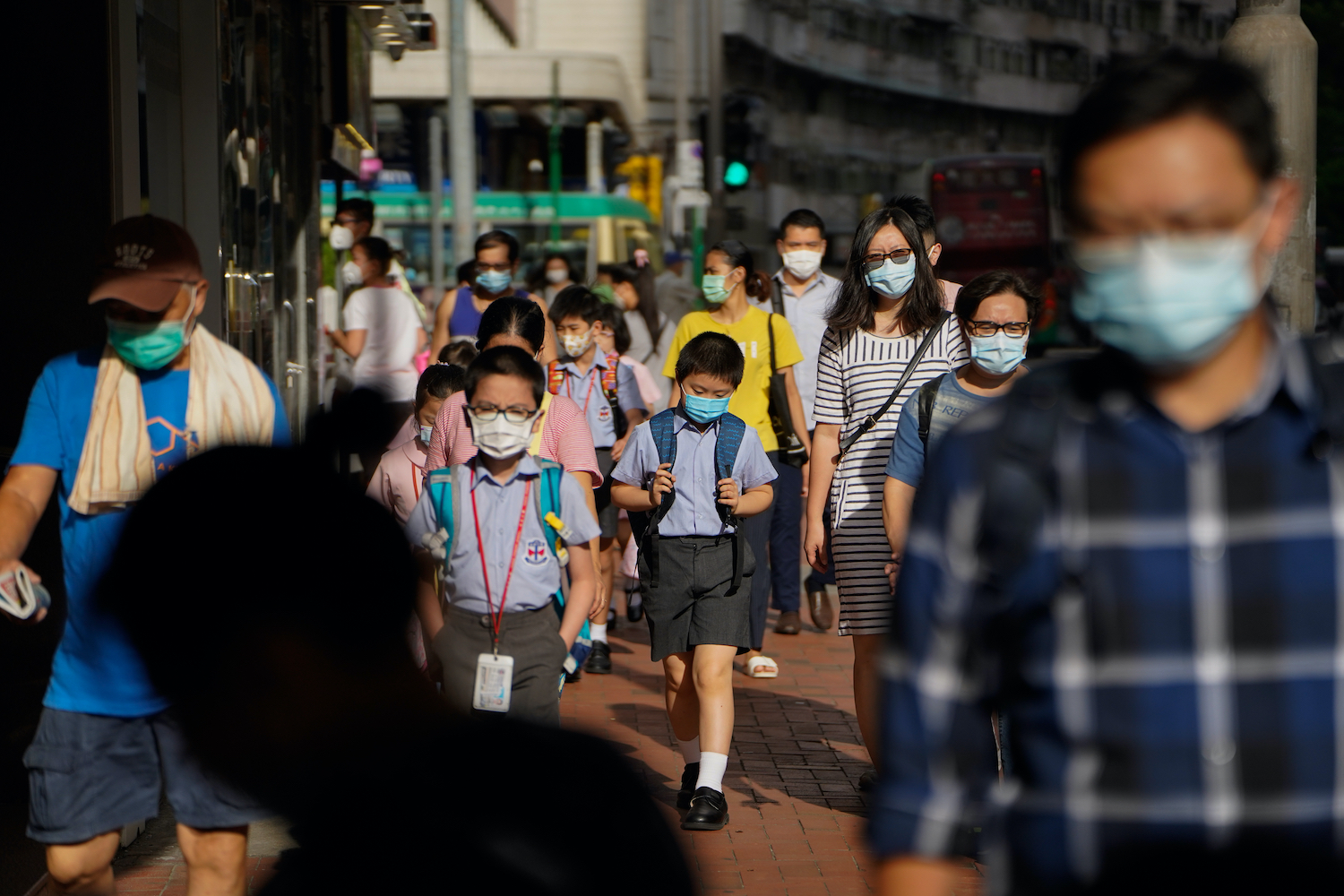 Schoolchildren wearing masks walk amid other pedestrians in Hong Kong on Friday. The territory is closing its schools again from Monday in hopes of keeping new virus cases from rising. (Bloomberg Photo)