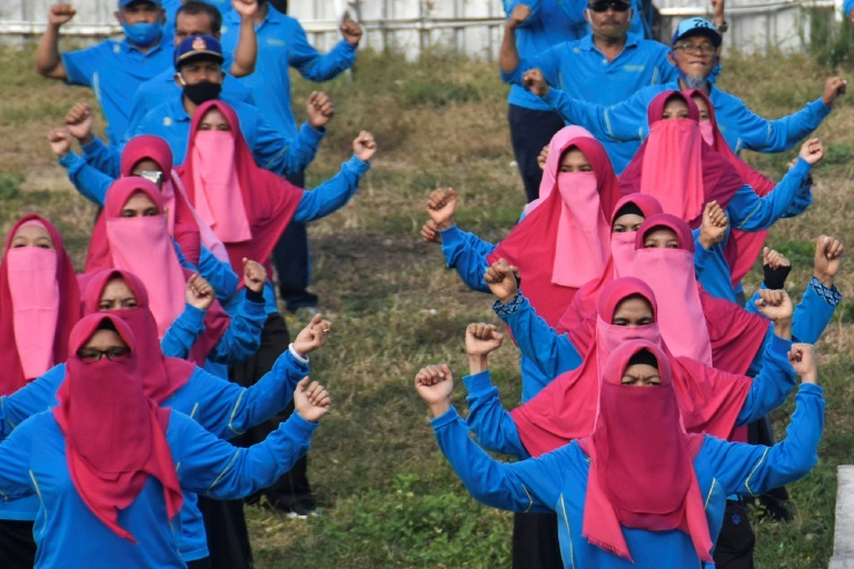 Female civil servants do morning exercises in Lombok, wearing veils instead of masks
