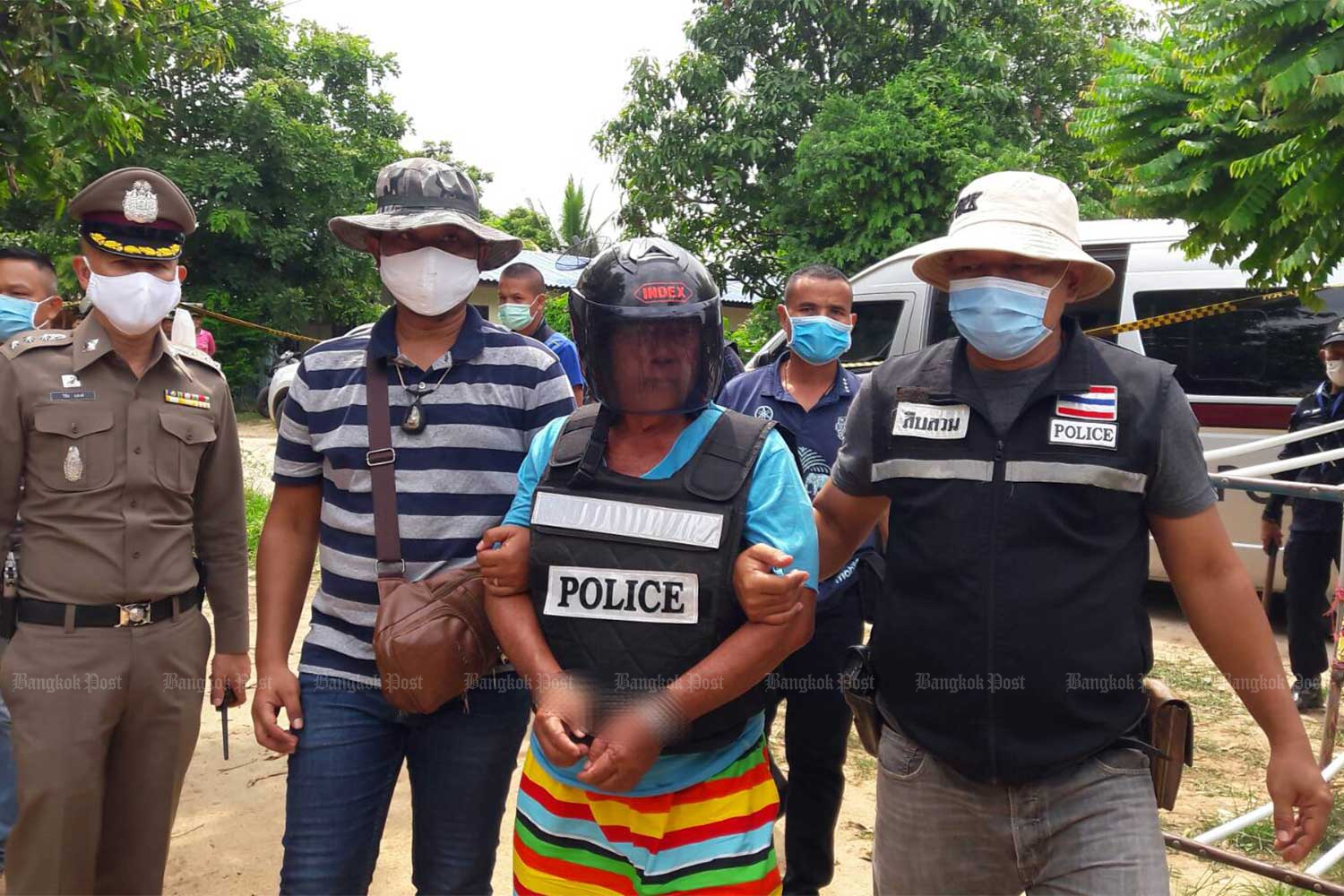 Police take murder suspect Amnuay Boonsong for a crime re-enactment in Chum Phuang district of Nakhon Ratchasima on Saturday.(Photo: Prasit Tangprasert)