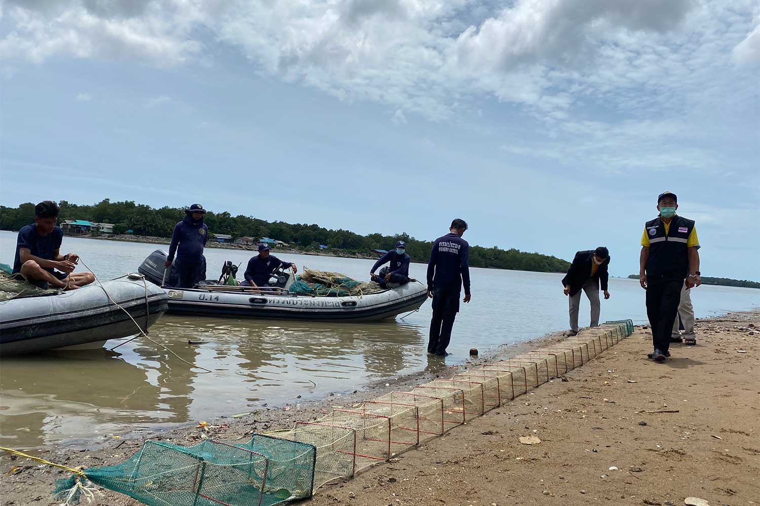 Officials examine an illegal fish trap seized from Bandon Bay in Surat Thani on Saturday. (Photo: Supapong Chaolan)