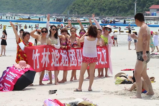 Chinese tourists enjoy the sand and surf on Koh Lan off Pattaya on June 8, 2018. (Post Today photo)