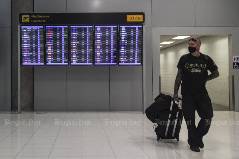 A traveller walks away from a panel displaying outbound flight information at Suvarnabhumi airport on Wednesday. (Photo by Arnun Chonmahatrakool)