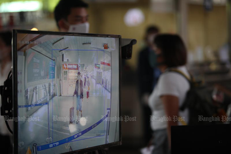 A screen shows temperatures of passengers entering BTS Phaya Thai station in Bangkok on Friday. (Photo by Apichart Jinakul)