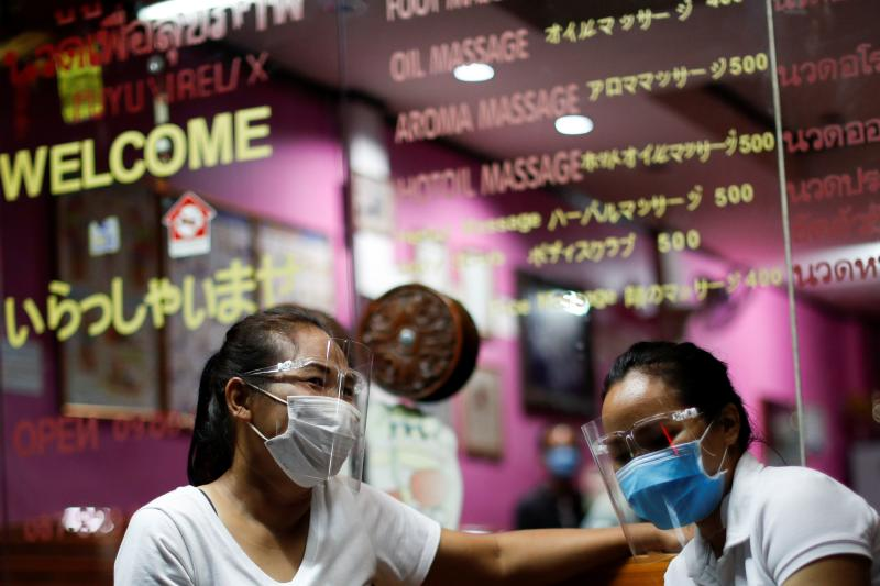 Therapists wearing face shields wait for costumers at a traditional Thai massage shop which reopened after the Thai government eased isolation measures to prevent the spread of the coronavirus disease in Bangkok, June 3, 2020. (Reuters file photo)