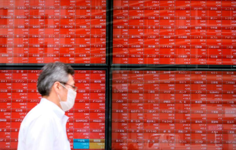 A pedestrian walks past an electronic quotation board displaying share prices of the Tokyo Stock Exchange in Tokyo on June 16, 2020. (AFP file photo)