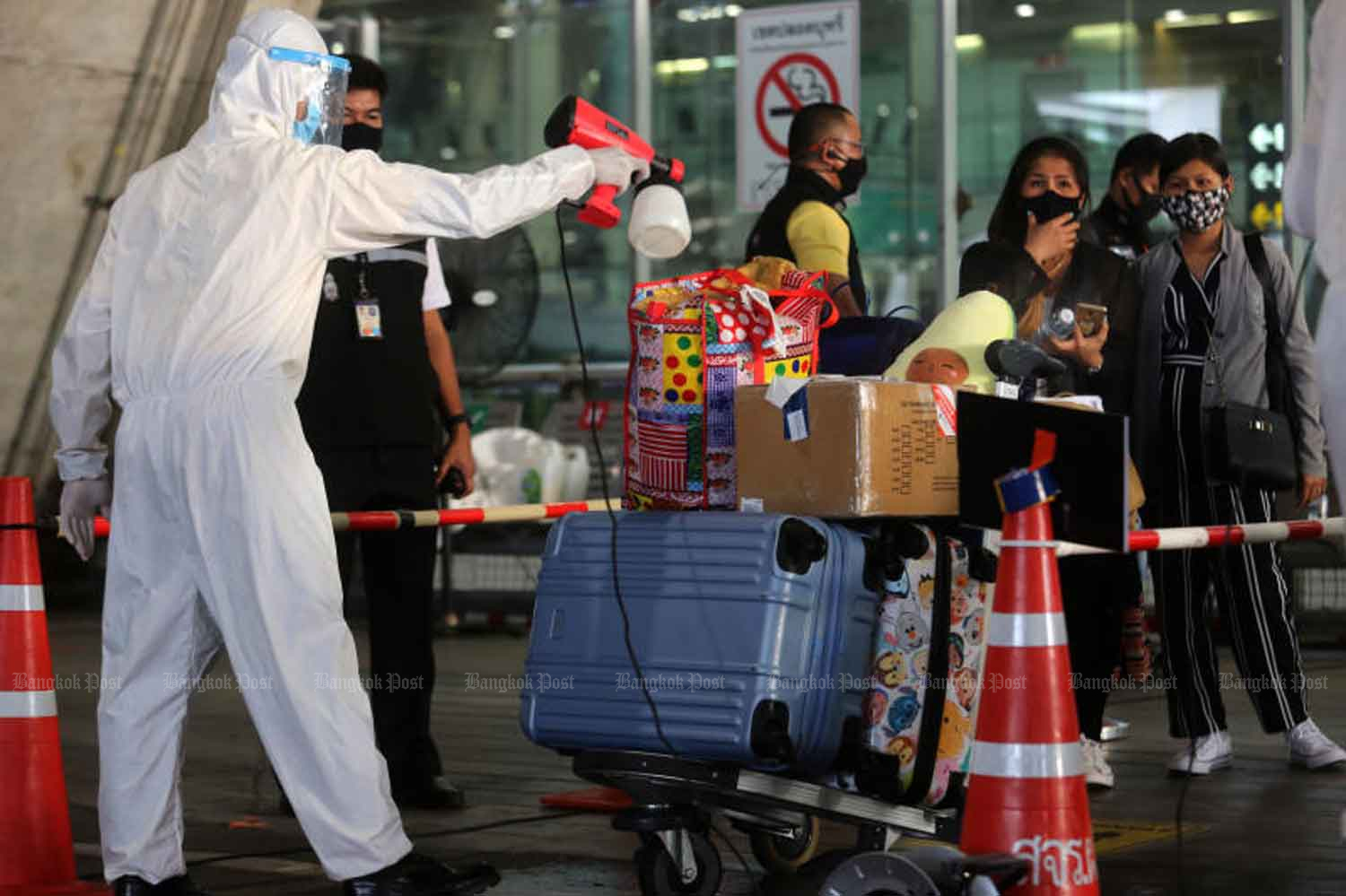 An airport official in protective gear sprays disinfectant on passengers' luggage at Suvarnabhumi airport as more Thais who had been stranded overseas and selected groups of foreigners continued to arrive in Thailand on Monday. (Photo: Wichan Charoenkiatpakul)