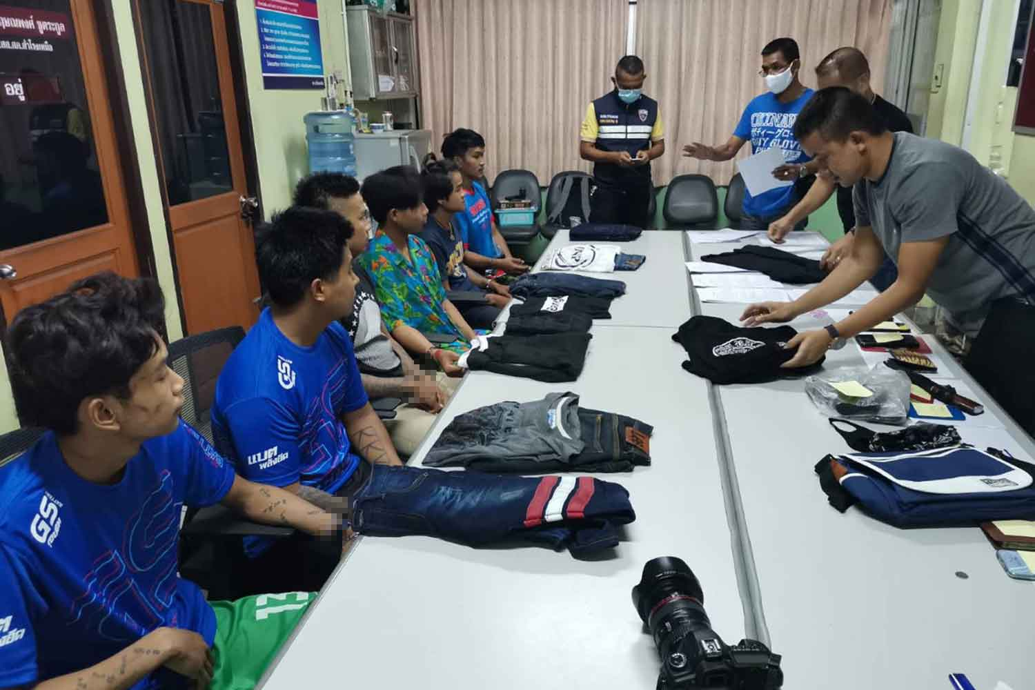 Six Myanmar men, seated left, were brought to Samrong Nua police station in Samut Prakan for questioning after a brawl at the Imperial World Samrong department store in which a Myanmar man was killed on Sunday. (Photo: Sutthiwit Chayutworakan)