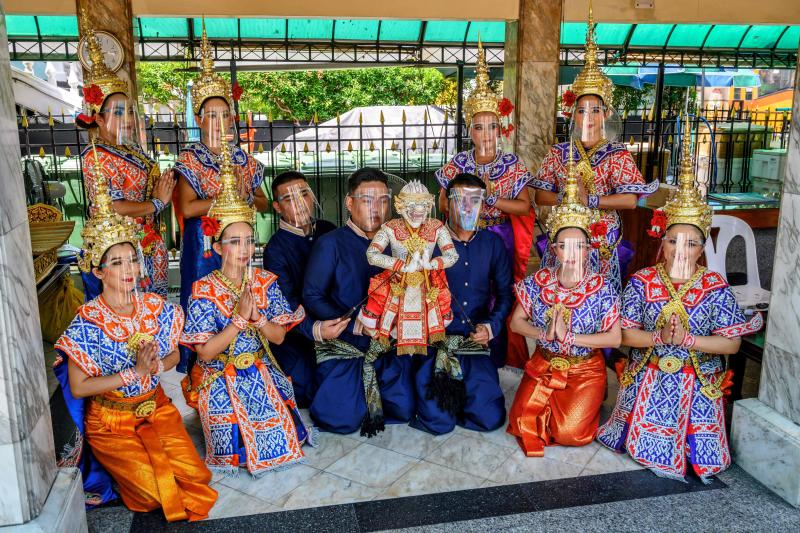 Dancers and puppeteers, all wearing protective face shields, pose for a photo with a Hanuman puppet at the Erawan Shrine in Bangkok on July 13, 2020. The Monkey God Hanuman is a character from the Ramakien, the Thai version of the Hindu epic Ramayana. (AFP photo)