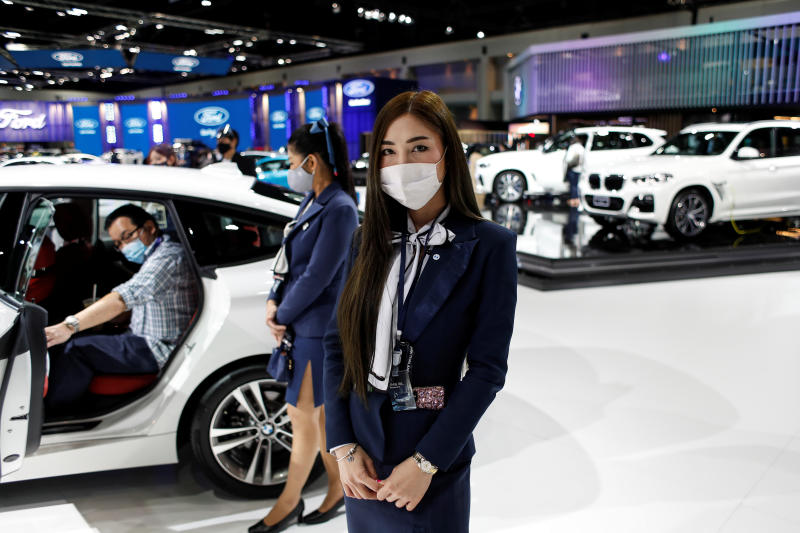 A representative of a BMW dealership wears a face mask during the media day of the 41st Bangkok International Motor Show after the Thai government eased measures to prevent the spread of the coronavirus disease (Covid-19) in Bangkok on Tuesday. (Reuters photo)