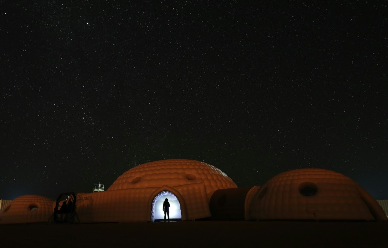A member of the AMADEE-18 Mars simulation mission wearing a spacesuit standing in the doorway of a simulation habitat, with a view of the night sky above in Oman's Dhofar desert, in February 2018