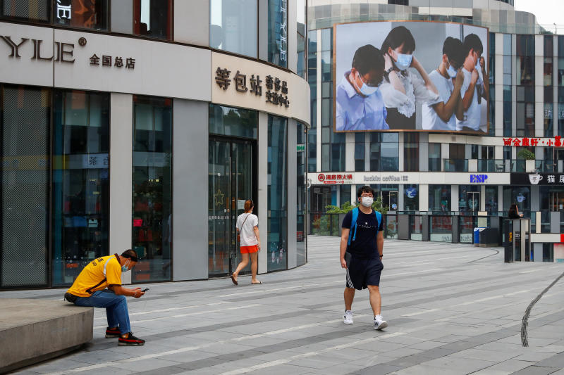 A man wearing a face mask walks near a screen showing a public health announcement reminding people to wear masks in public at a shopping area in Beijing on Monday. Duty-free sales on Hainan island surged in July. (Reuters photo)
