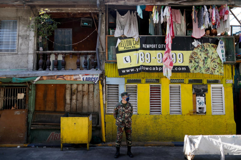 A soldier wearing a protective mask guards a street while children look out from a balcony, as the city undergoes a stricter lockdown to contain the coronavirus disease ) spread, in Pasay City, Philippines, April 22, 2020. (Reuters file photo)