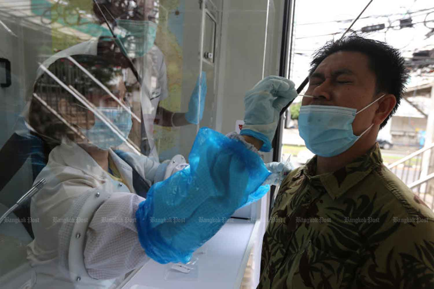 A health official takes a nasal swab from a person at Passione Shopping Destination (Laemtong) mall in Rayong province on Tuesday. The Disease Control Department said on Wednesday there was only a small chance someone may have caught Covid-19 from the infected Egyptian soldier.(Photo: Wichan Charoenkiatpakul)