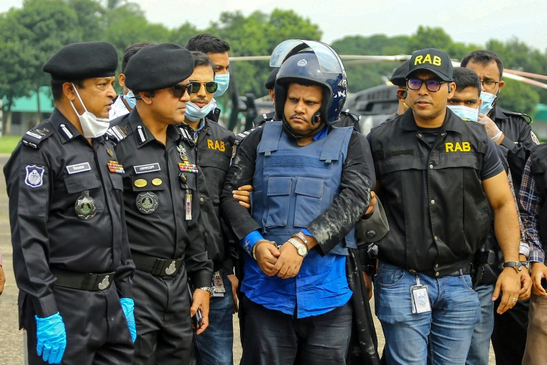 Police escort Bangladesh hospital owner Mohammad Shahed after his arrest for distributing fake certificates saying thousands of patients had tested negative for Covid-19.