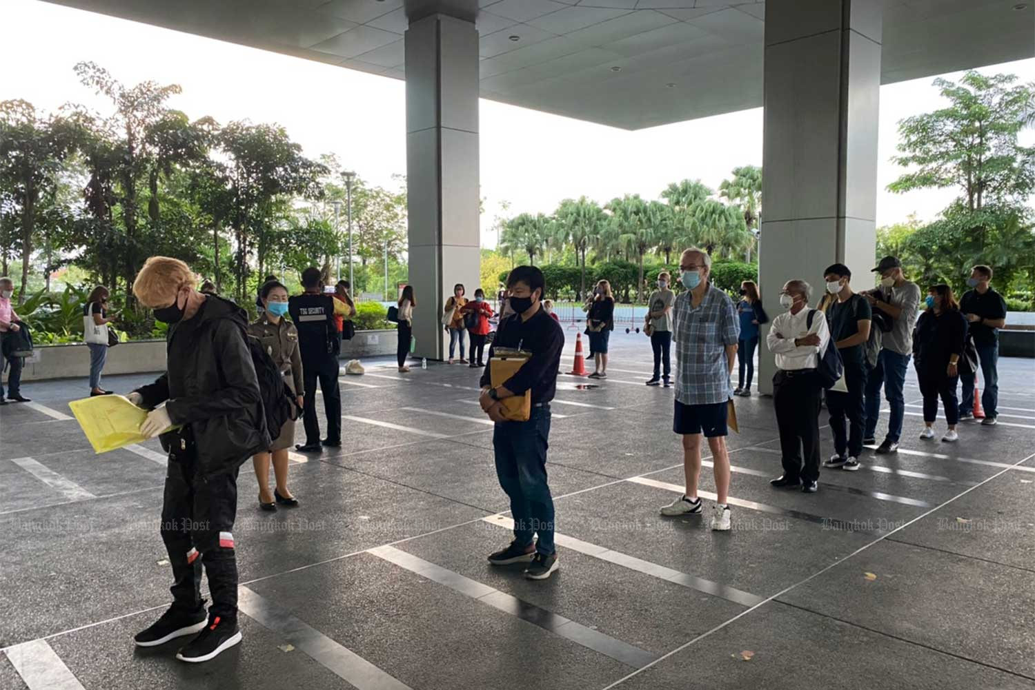 Foreigners wait at the Immigration Bureau's temporary office at the Central Investigation Bureau Building in Muang Thong Thani last week, seeking visa extensions after the Covid-19 pandemic disrupted their travel plans. (Immigration Bureau photo)