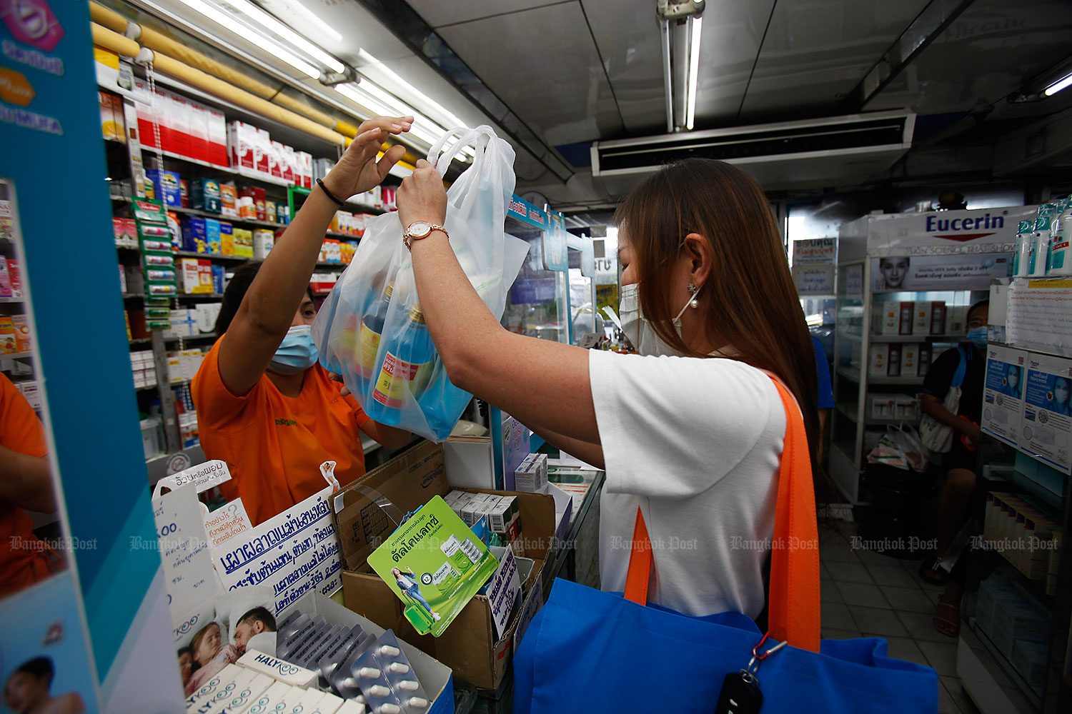 Keeping it clean: A woman buys bottles of alcohol at a chemist's on the opposite side of the Ying Charoen Market to make into hand sanitiser. People nationwide have become fearful over a potential second wave of Covid-19 possibly being triggered by a visiting Egyptian airman and the young daughter of a diplomat who both tested positive for the virus. (Photo by Nutthawat Wicheanbut)