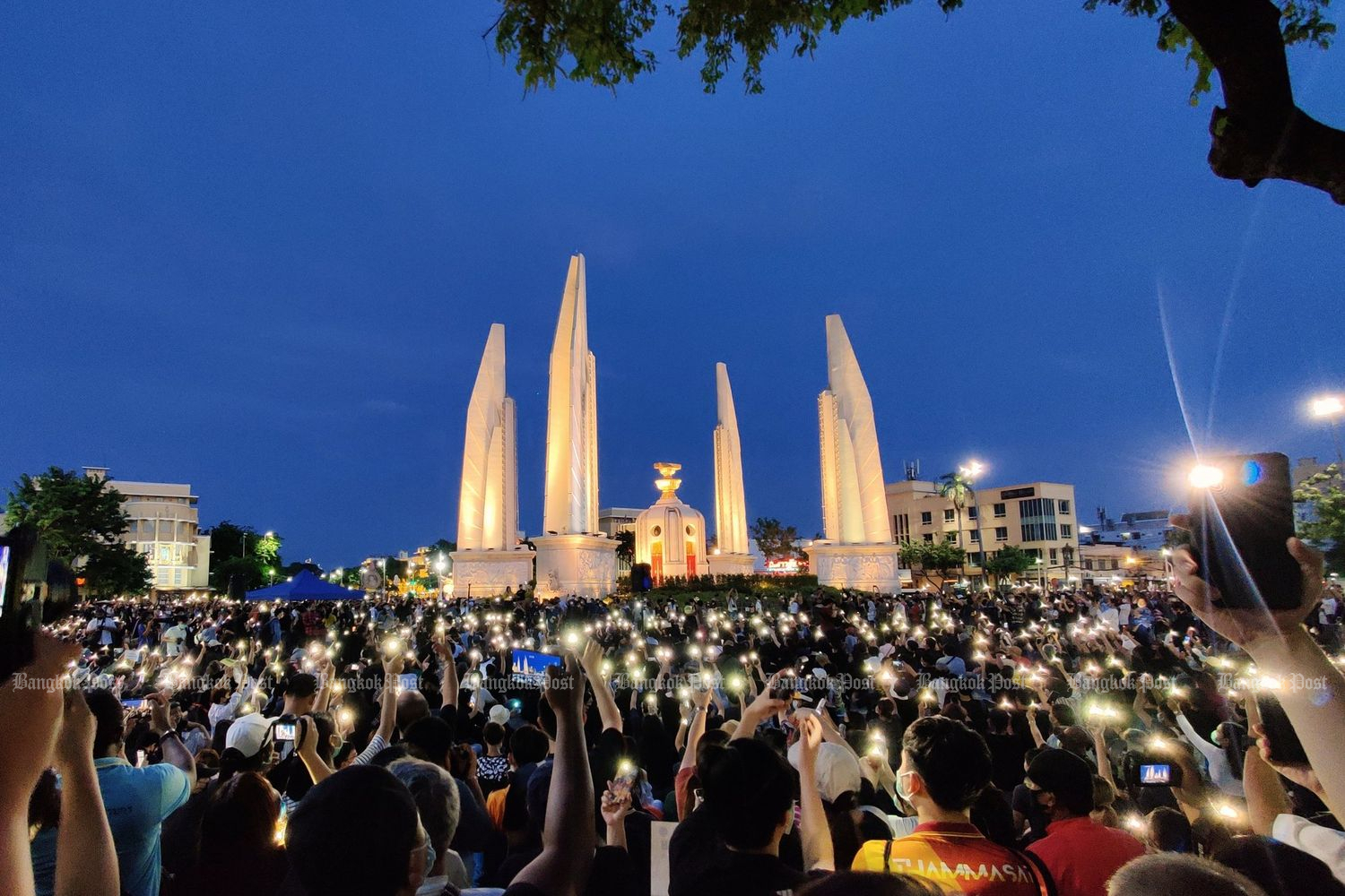Protesters raise their smartphones in the symbolic gesture of shining a light on Democracy Monument in Bangkok on Saturday evening. (Photo courtesy of jo @Ponlapatz)