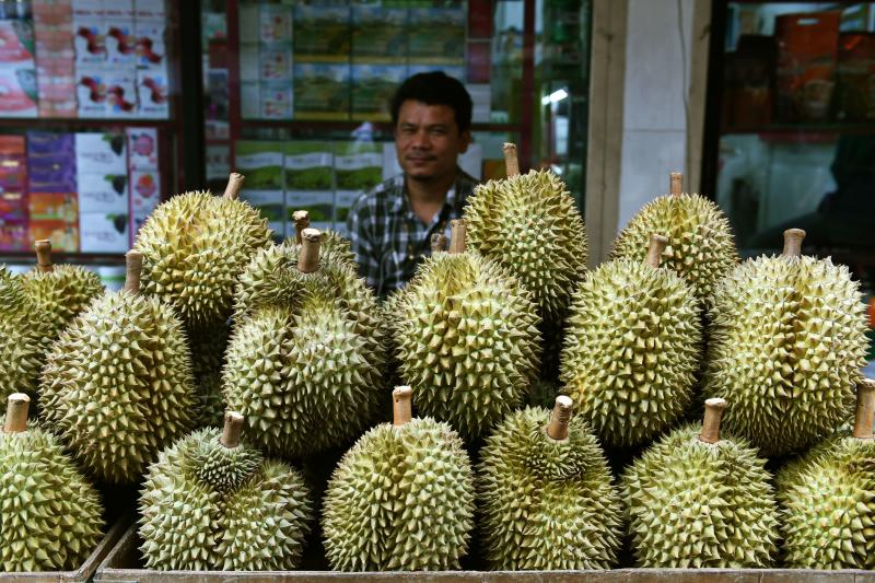 A fruit vendor waits for customers behind a diplay of durians in Bangkok on June 1, 2018. (AFP photo)