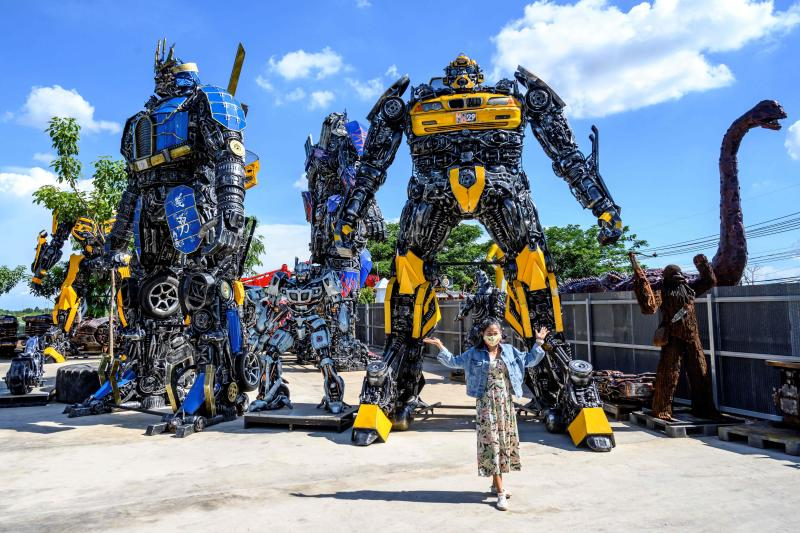 This photograph taken on July 18, 2020 shows a tourist posing for photos in front of life-sized sculptures of characters from the