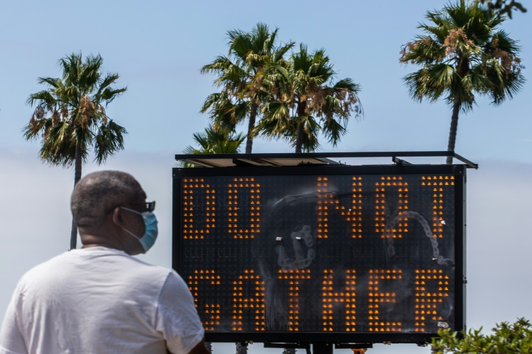 In the middle of summer vacation season, a sign urges people not to gather in Long Beach, California.