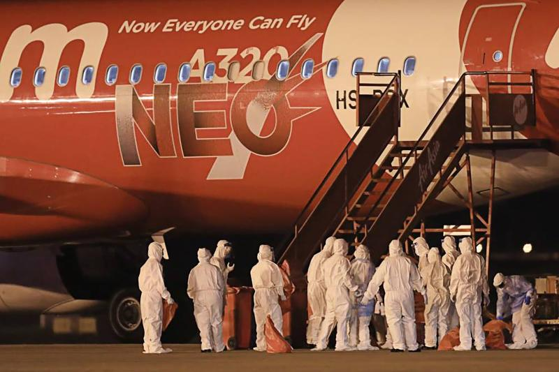 In this handout file photo from the Royal Thai Navy taken and released on Feb 04, 2020 navy officials in protective suits stand beside a plane that brought Thai nationals back from Wuhan, the first epicentre of the novel coronavirus outbreak, at the military U-Tapao Airport in Rayong. (