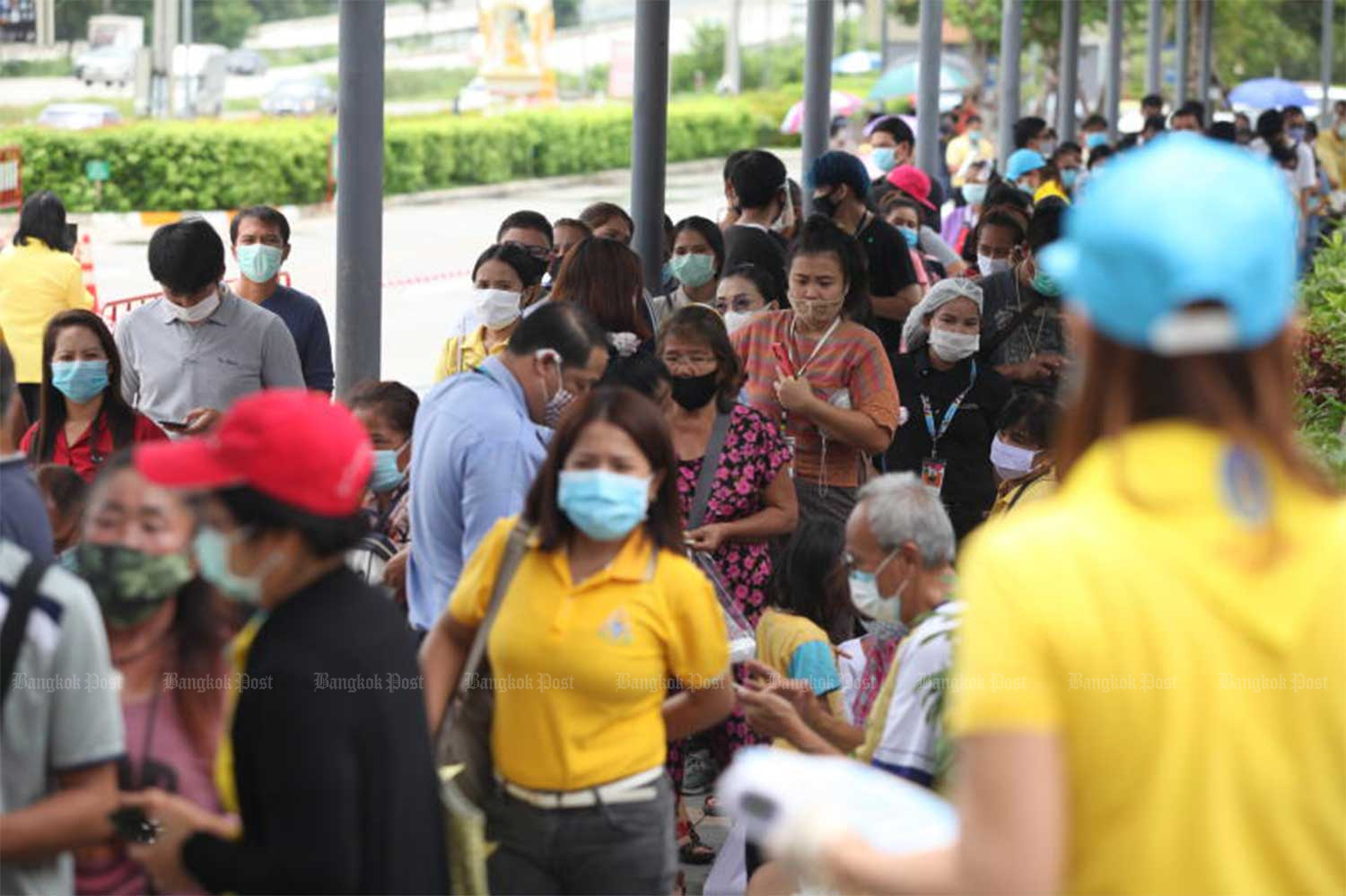 Hundreds of people tracked down through the Thai Chana app queue to be tested by disease control officials at CentralPlaza Rayong department store on July 14. More people were tested in Rayong on July 20. All tests have returned negative. (Bangkok Post file photo)