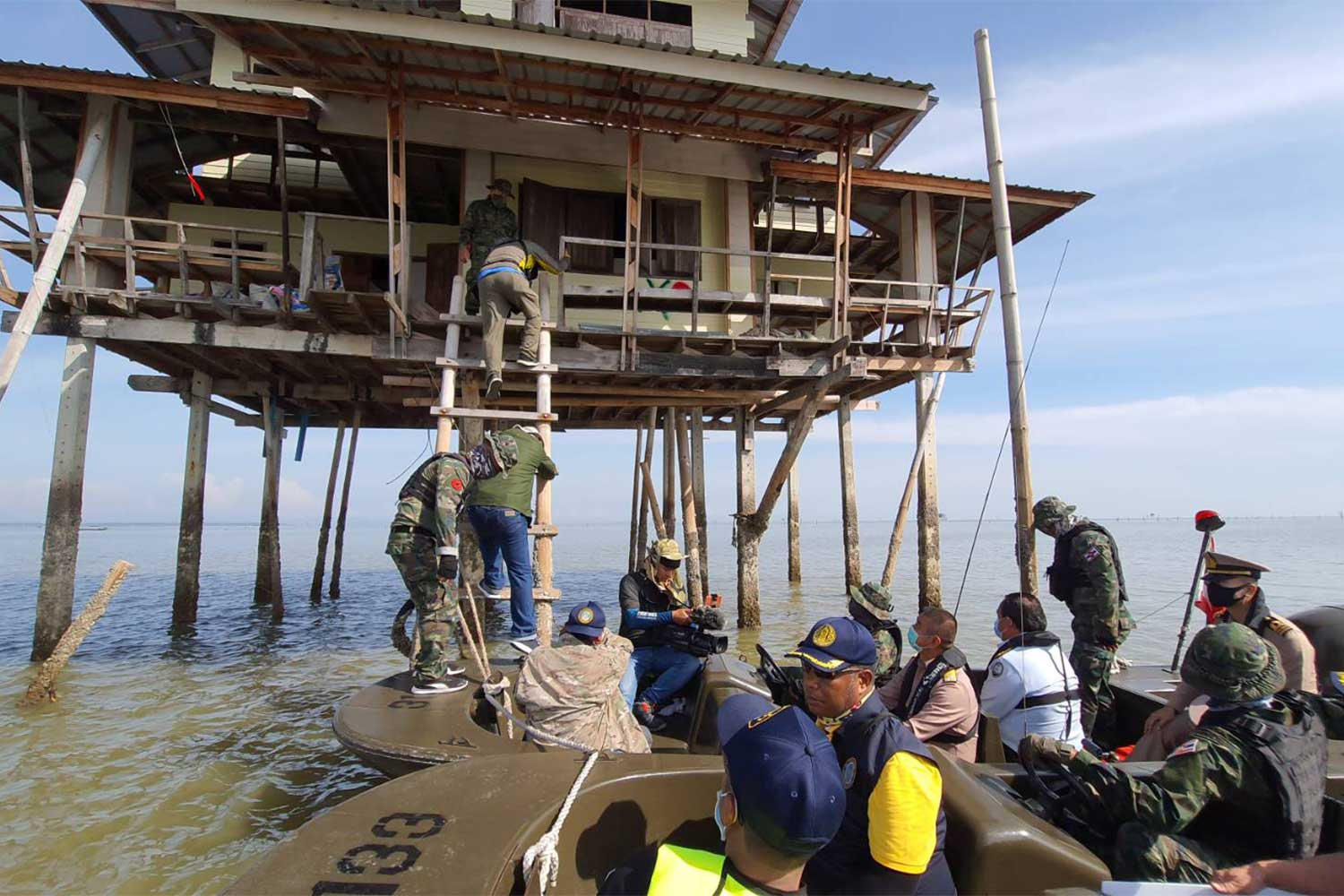 Navy sailors post a dismantle order at one of 176 illegally built roofed platforms in the public waters of Bandon Bay in Surat Thani on Tuesday. (Photo: Supapong Chaolan)