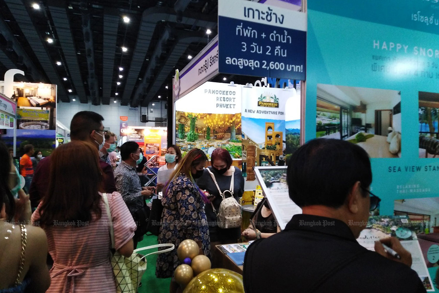 Visitors browse local trip deals at a travel fair. The cabinet on Tuesday approved three categories of unlicensed hotels to participate in the We Travel Together tourism stimulus campaign. (Photo by Dusida Worrachaddejchai)