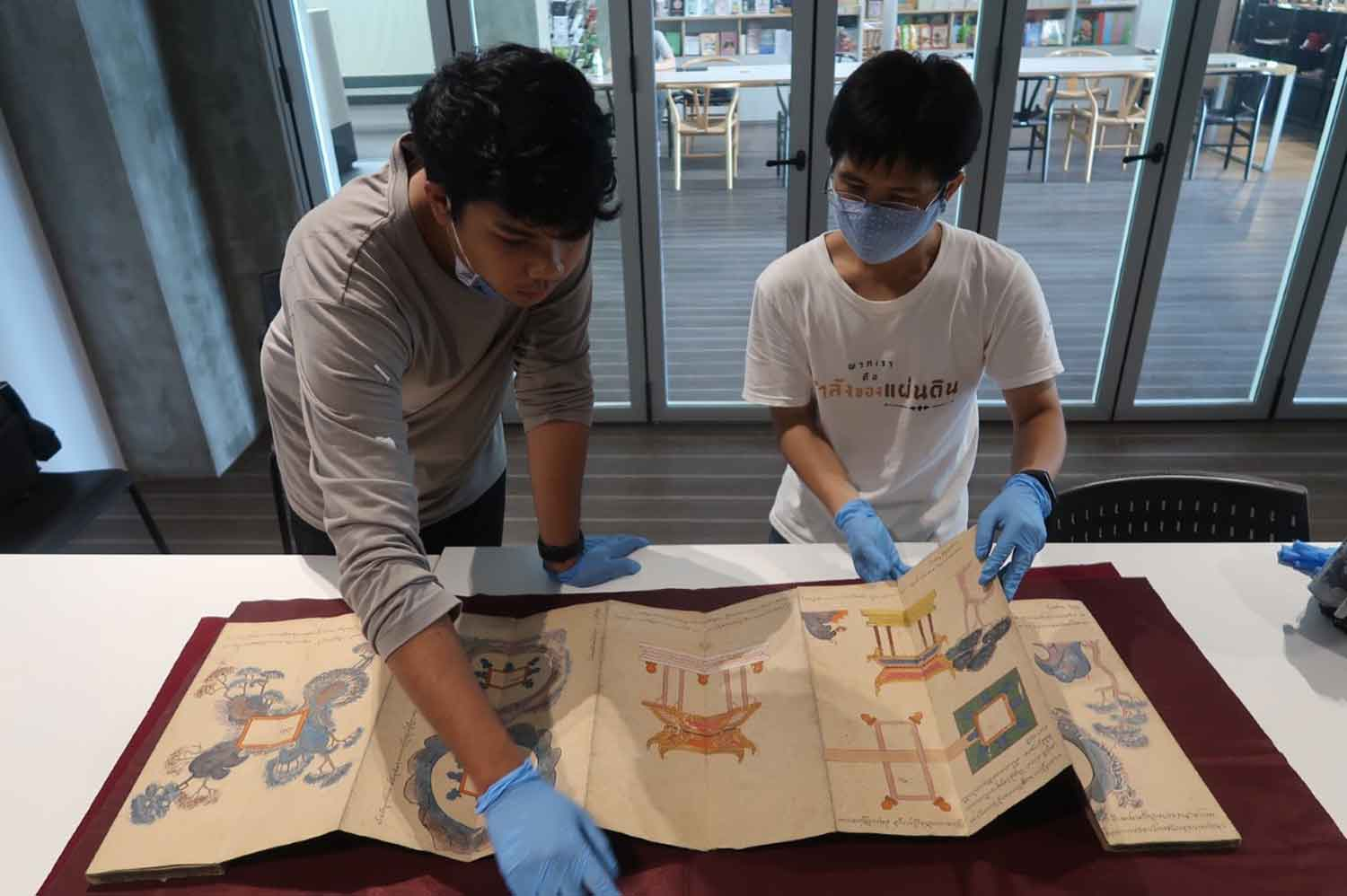 Officials examine an old folding book returned to the Arts and Cultural Centre of Nakhon Si Thammarat Rajabhat University on Sunday. Hundreds of ancient manuscripts are believed to have been stolen from the centre. (Photo: Nujaree Raekrun)