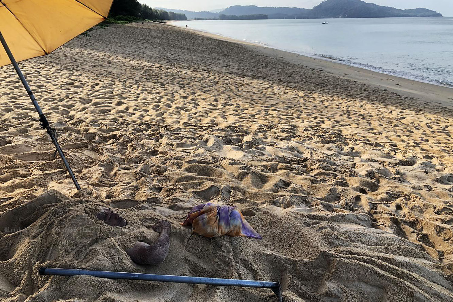 A man is buried in the sand on Hat Mai Khao Beach in Phuket as he believes it can help cure his paralysed limbs. (Sarot Meksophawannakul)