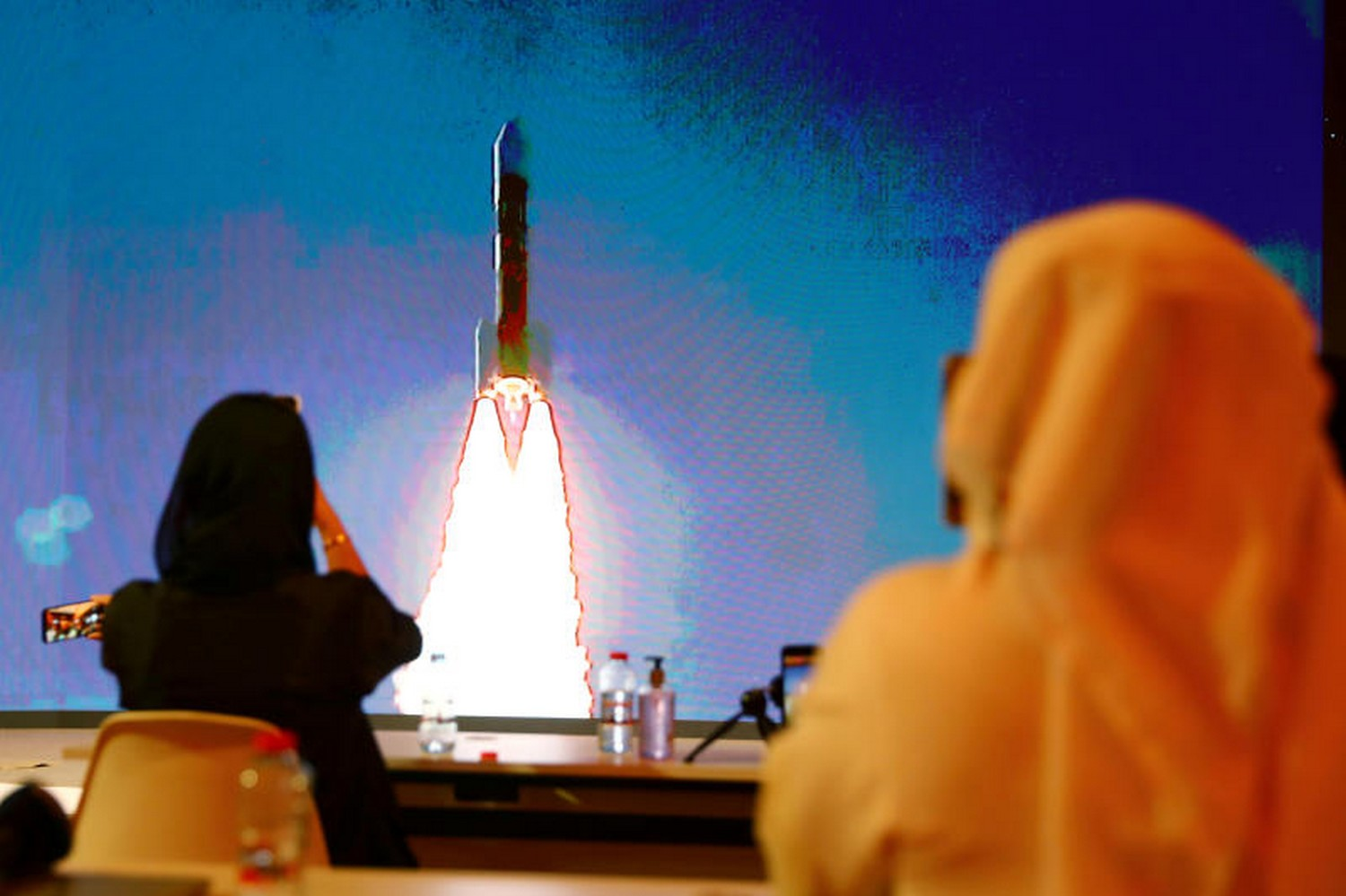 People watch a big screen displaying the launch of the Hope Probe from Tanegashima Island in Japan at the Mohammed bin Rashid Space Centre in Dubai United Arab Emirates on July 20