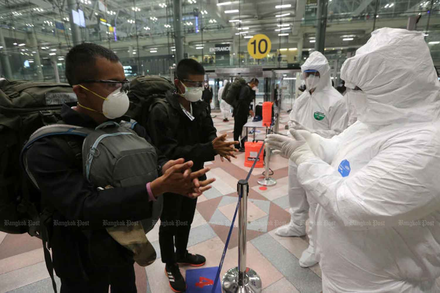 Health officials show soldiers returning from a military exercise in Hawaii how to sanitise their hands at Suvarnabhumi airport in Samut Prakan province on Thursday, when the government confirmed eight new Covid-19 cases among already quarantined returnees. (Photo: Wichan Charoenkiatpakul)