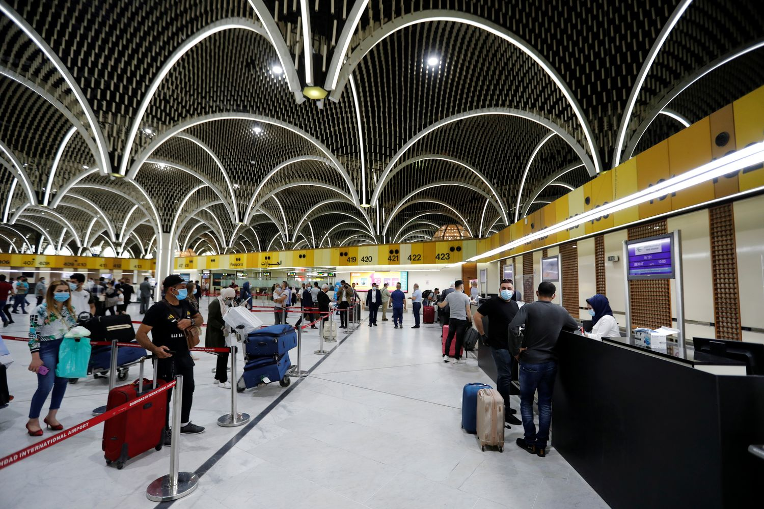 Passengers wearing protective masks line up to check-in after the reopening of Baghdad International Airport, where flights halted due to the coro0navirus outbreak in Baghdad on Thursday. (Reuters photo)