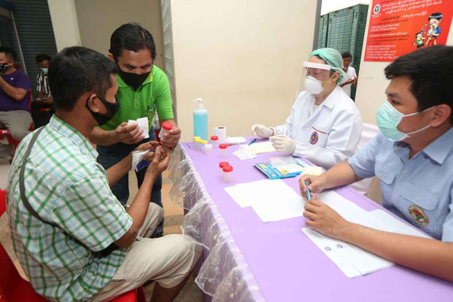 Health volunteers take part in an activity to raise awareness about Covid-19 among migrant labourers in Muang district in Samut Sakhon province in April. (Photo by Varuth Hirunyatheb)