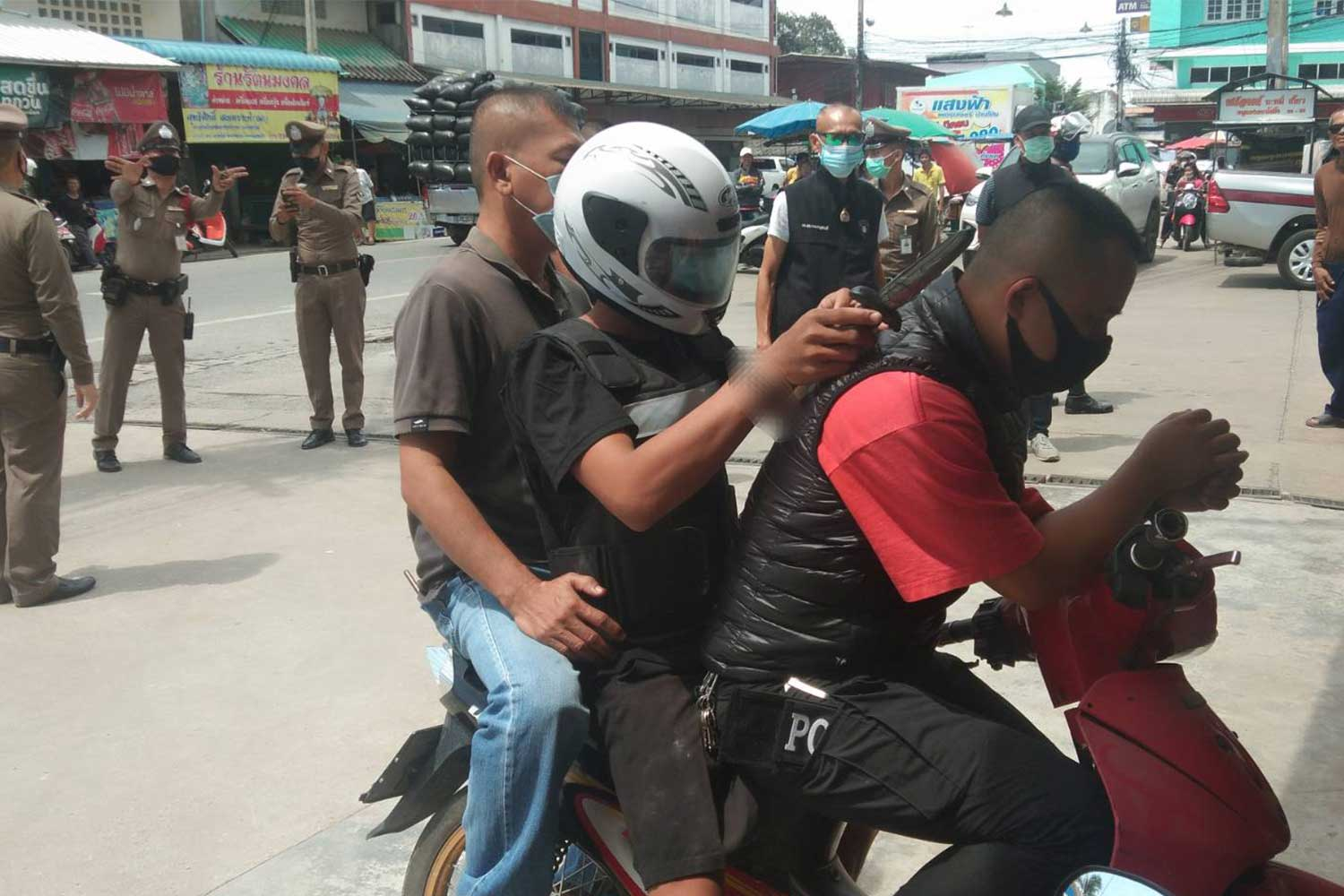 The 21-year-old accused robber, wearing a full-face crash helmet, is taken for a crime re-enactment at a 7-Eleven store in Tha Maka district, Kanchanaburi, on Friday following his arrest on Thursday night. The suspect and a 17-year-old accomplice are charged with holding up the store and taking a young woman employee hostage in the early hours of Thursday. (Photo by Piyarach Chongcharoen)